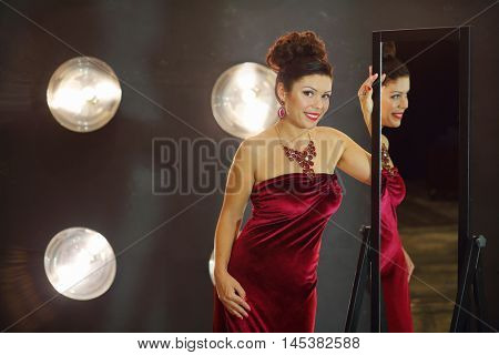 Woman in red smiles and looks at camera near mirror in studio with lamps on wall