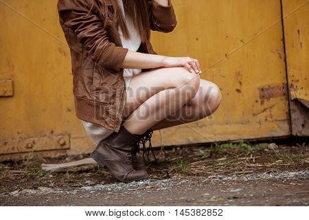 Fashion Model Girl on the Industrial Background. Detail of Clothes. Slim legs in brutal boots.