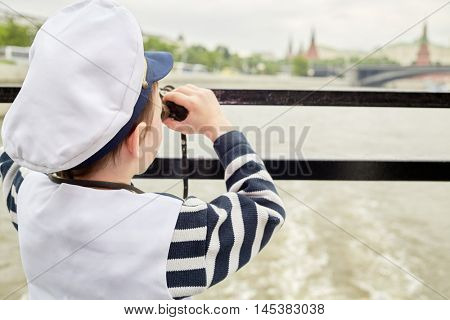 Little boy dressed as a captain looks through binoculars standing at boat stern, rear view.