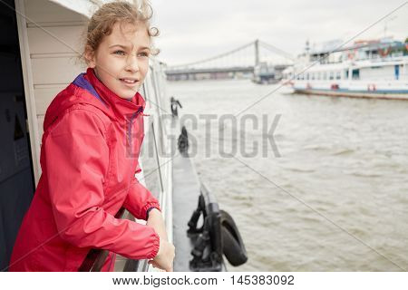 Girl in red jacket at railing on pleasure boat deck.