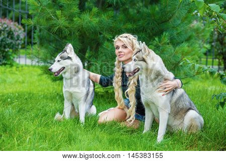 Young blond woman with two Husky dogs sits on grass under pine in summer park.