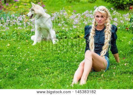 Young barefoot blond woman sits on grassy lawn in park, dog sits behind her out of focus.