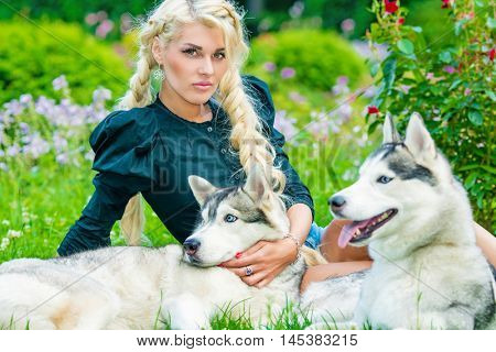 Young blond woman plays with two Husky dogs sitting on grassy lawn in summer park.