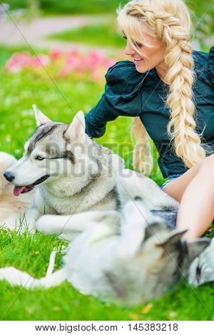 Young blond woman plays with two Husky dogs sitting on grass in summer park.