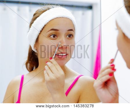 Attractive young woman wearing pink top and white headband, squeezing nose with flat tweezers, looking in mirror smiling.