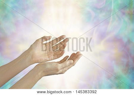 Energy healer with open hands - female hands sensing life force energy with open palms on a beautiful pastel misty energy formation background