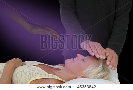 Spiritually Assisted Healing Session -  male healer channeling healing energy to supine resting female with the help of a spirit healing guide