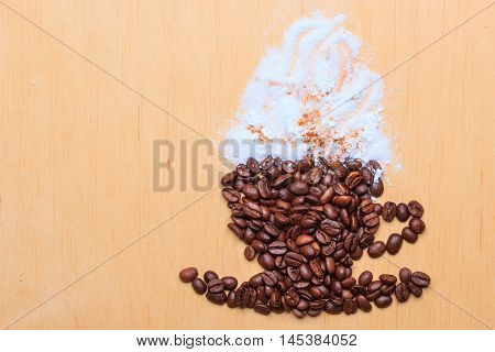 Cappuccino time. Roasted coffee beans placed in shape of cup and saucer with cinnamon white froth on wooden surface background
