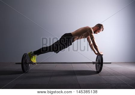 one man exercising fitness plank position exercises in studio silhouette isolated dark key