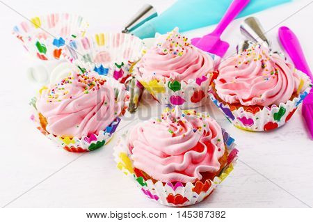 Homemade pink birthday cupcakes and cookware background. Birthday cupcake with pink whipped cream. Homemade cupcakes decorated for party.