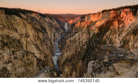 First morning light at Lower Falls Yellowstone river Grand canyon of the Yellowstone National Park. Clear sky morning with water fall and river through very steep canyon. Beautiful view of outdoor park in Wyoming USA.