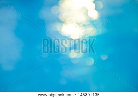 Bokeh Light Effects Over A Rippled, Blue Water Background