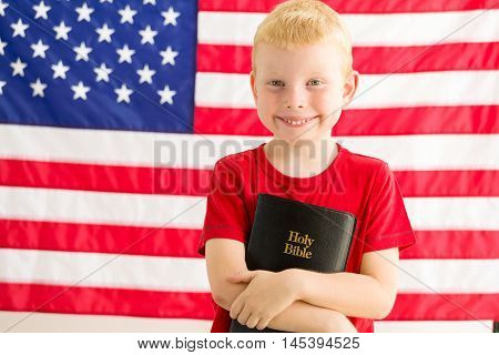 Christian Boy Holding Holy Bible In Front Of American flag
