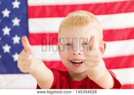 Little boy in front of American flag with thumbs up