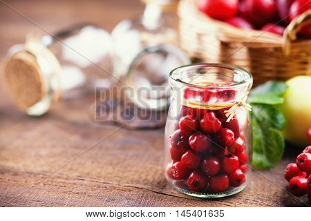 Glass jar with rowanberry and plums in a basket