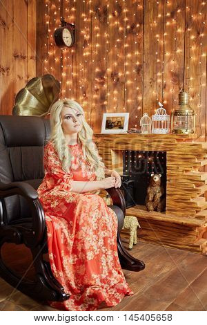 Blond woman in red dress sits in rocking-chair in room with fireplace and wall decorated with luminous garland.