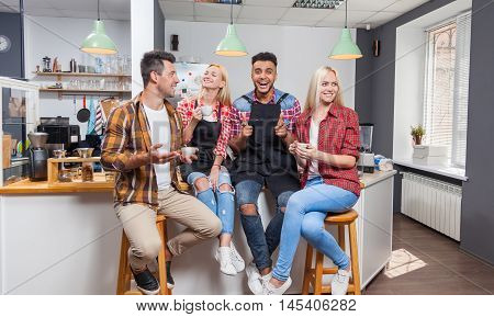 People friends drinking coffee shop talking laughing with barista sitting at bar counter, mix race man and woman happy smile