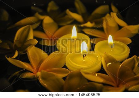 Three floating lighted candles among Plumeria on water