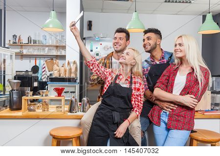 People taking selfie friends pictures drinking coffee shop with barista sitting at bar counter, mix race men hold smart phone woman happy smile