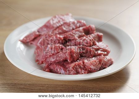raw fresh sliced beef for beefsteaks in plate on kitchen table, shallow focus