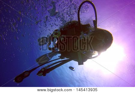 A backlit scuba diver silhouette. View of the scuba diver gear fins regulator mask and bubbles underwater in the deep blue sea of Limassol Cyprus against the sunlight.