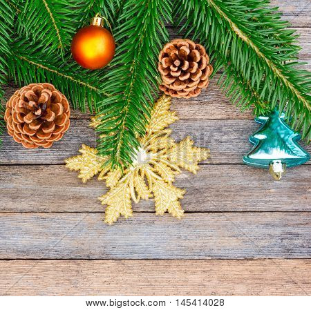 New Year or Christmas background: fir branches colorful glass balls and golden snow-flake cones over old wooden backdrop top view copy space