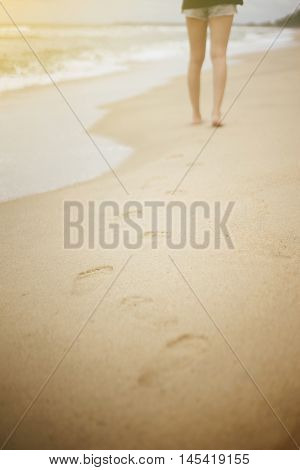 Beach Travel - Young Woman Walking On Sand Beach Leaving Footprints In The Sand. Closeup Detail Of F