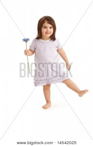 Cute little girl with flower in spring dress, standing on one foot.?