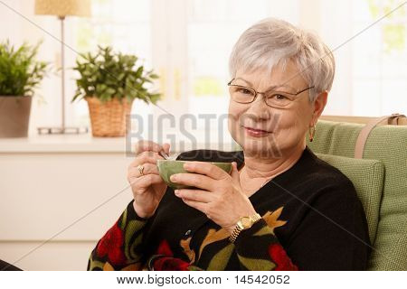 Portrait of senior lady drinking tea at home, holding cup, looking at camera, smiling .?
