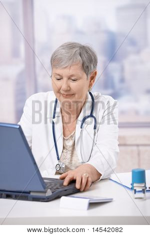 Senior female doctor, working at desk, using laptop computer. Looking at screen, smiling.?