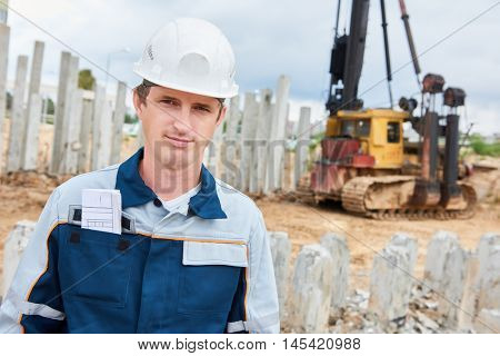 construction worker foreman in front of pile driver machine