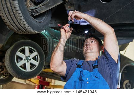Automobile mechanic checks car suspension in service station