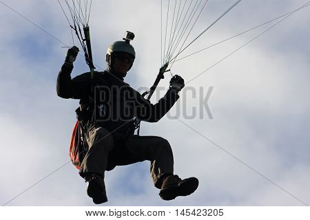 Paraglider in silhouette against a blue sky
