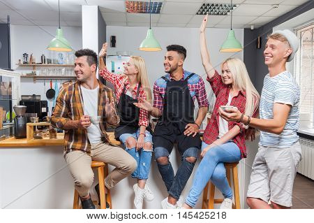 People friends drinking coffee shop talking laughing with barista sitting at bar counter, mix race man and woman happy smile wave hands raised up