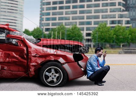 Image of frustrated businessperson screaming on the cellphone in front of a damaged car after collision