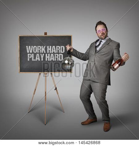Work hard play hard text on  blackboard with drunk businessman