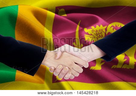 Picture of a negotiation handshake with two entrepreneur hands closing a deal and shaking hands in front of a national flag of Sri Lanka