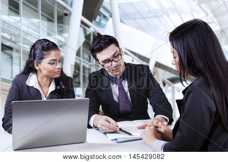 Portrait of two business people showing an employment contract on a new employee in the office
