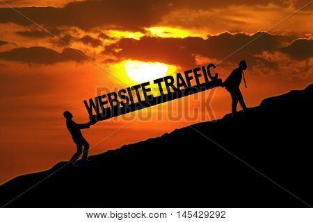 Silhouette of two businessmen walking on the hill while carrying text of website traffic at sunset time