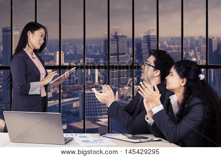 Two young business people clapping hands for their partner after business presentation