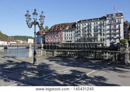 LUCERNE SWITZERLAND - MAY 05 2016: Colorful townhouses down by the river Reuss shows the unique character of the city and variety of sightseeing attractions. The town is a destination for many travelers