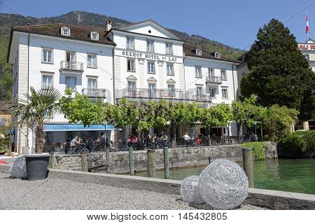 Weggis Switzerland - May 05 2016: Hotel centrally located in the city on the banks of the Lake Lucerne provides the perfect place to spend a nice time and enjoy wonderful views of nature. Several people in the outdoor restaurant can be seen. Weggis it is