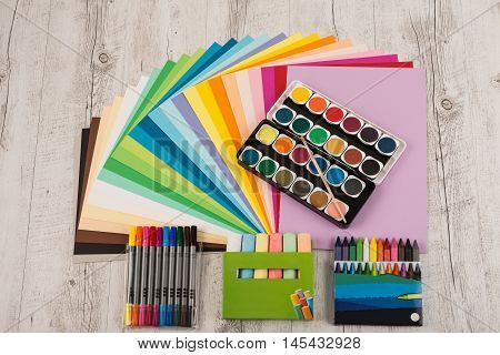 Sheets of colored paper, iridescent palette of colored paper, rainbow colors, rainbow colors, watercolors, wax crayons, colored markers, crayons on the wooden table