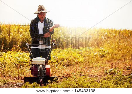 Farmer is working with cultivator machine. Sunny day.