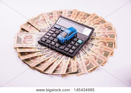 blue toy car with Indian currency notes or money with note pad, spectacles,calculator pen and coins