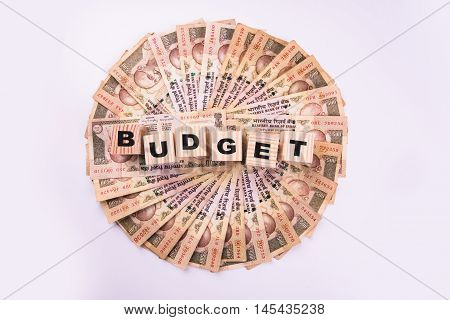 indian currency notes arranged in circular shape and budget text written on wooden blocks