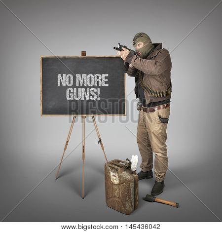 No more guns text on blackboard with man holding machine gun