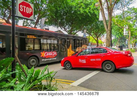 SINGAPORE, REPUBLIC OF SINGAPORE - JANUARY 08, 2014: City public transport of Singapore. The bus in the movement and a city taxi