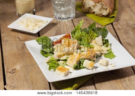 ceasar salad on a white plate on rustic wood