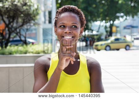 Thinking african american girl with yellow shirt and short hair outdoor in the city in the summer